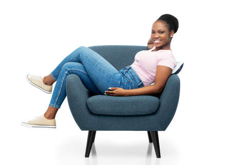 smiling african american woman sitting in armchair Stock Photo