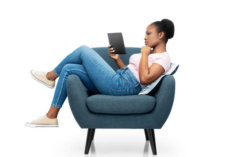 woman with tablet pc sitting in armchair