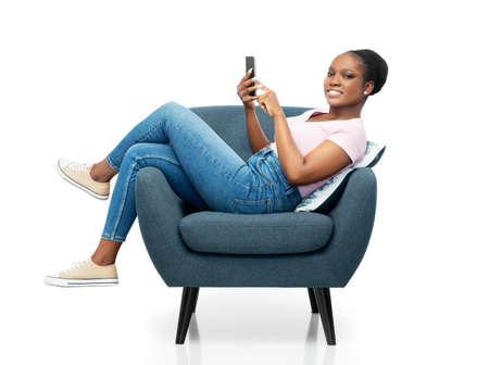 african american woman with smartphone in armchair