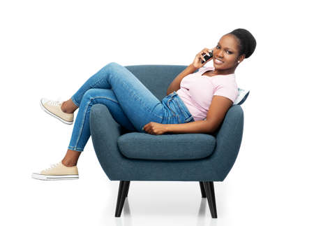african woman calling on smartphone in armchair