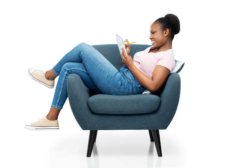 happy young woman in armchair writing to notebook