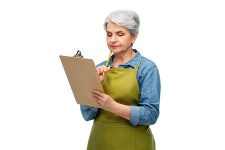 senior woman in garden apron with clipboard