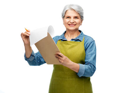 smiling old woman in garden apron with clipboard