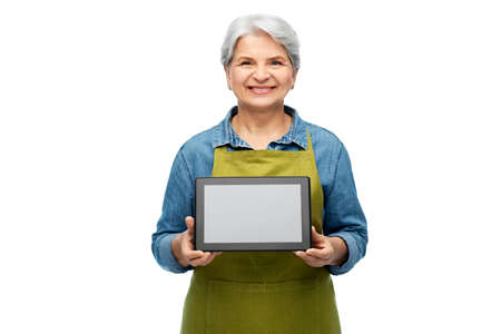 happy senior woman in garden apron with tablet pc