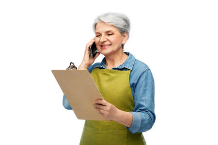 old female gardener with clipboard calls on phone