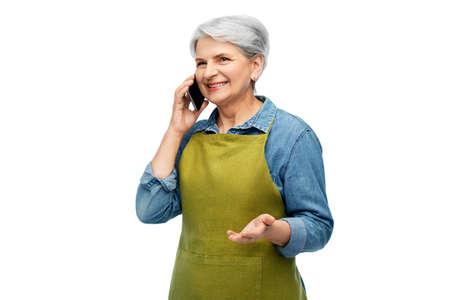 senior woman in garden apron calling on smartphone