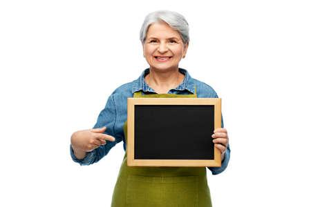 happy senior woman in garden apron with chalkboard Stock Photo