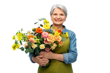 smiling senior woman in garden apron with flowers Stock Photo