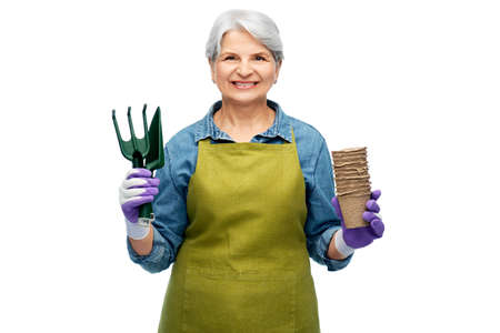old woman in apron with pots and garden tools