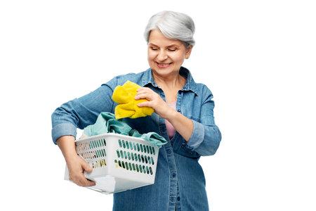 smiling senior woman with laundry basket