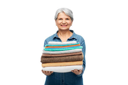 smiling senior woman with clean bath towels