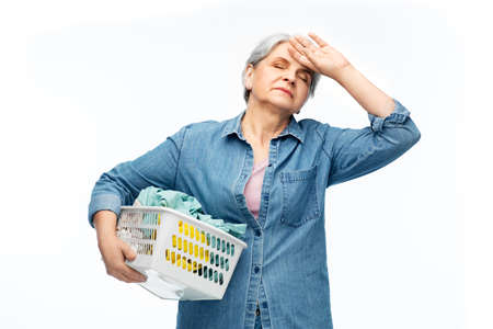 tired senior woman with laundry basket