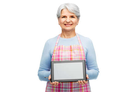 smiling senior woman in apron with tablet computer