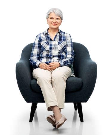 smiling senior woman sitting in modern armchair