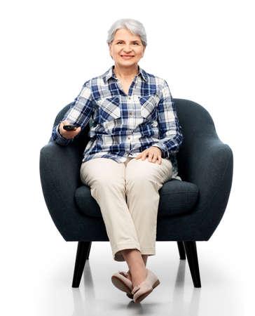 happy senior woman watching tv sitting in armchair Stock Photo