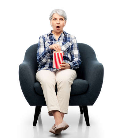 senior woman eating popcorn sitting in armchair Stock Photo