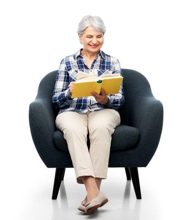 senior woman reading book sitting in armchair