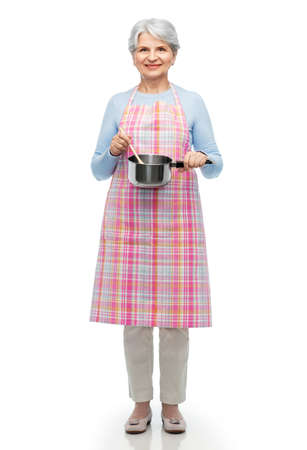 senior woman in apron with pot cooking food Stock Photo