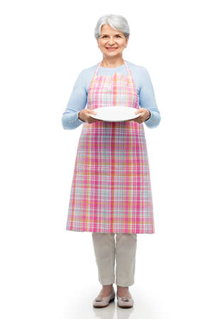 smiling senior woman in apron with empty plate