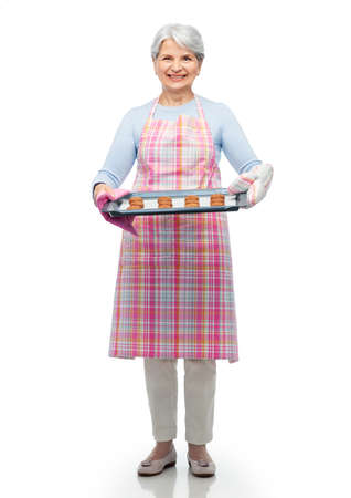 senior woman in apron with cookies on baking pan