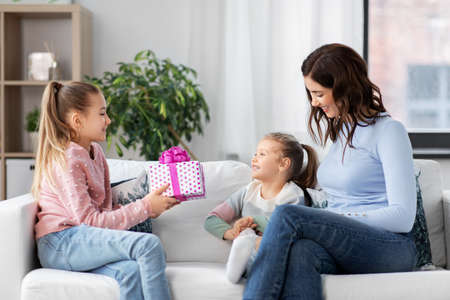 girl giving present to younger sister at home