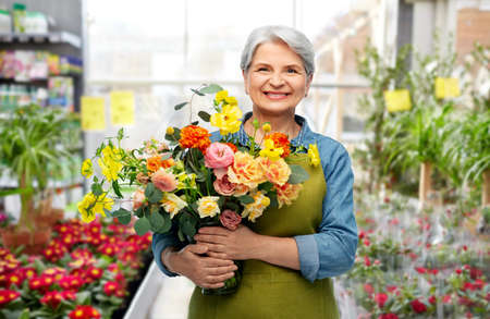 smiling senior woman with flowers at garden store