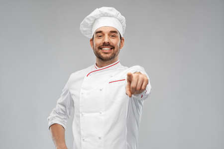 happy smiling male chef in toque pointing to you Banque d'images