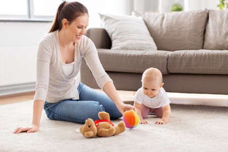 happy mother playing with little baby at home