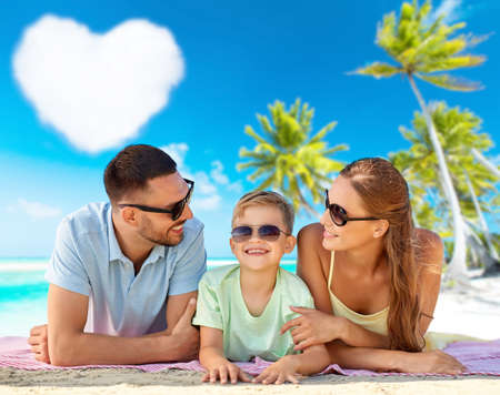 happy family lying over tropical beach background