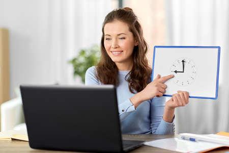 teacher with clock having online class at home