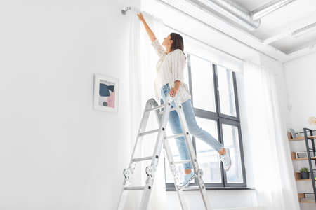 woman on ladder hanging curtains at home