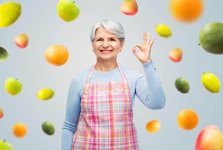 smiling senior woman in apron showing ok gesture Stockfoto