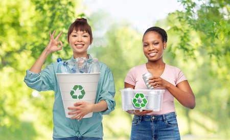 happy women sorting plastic and metallic waste Фото со стока