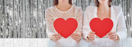 close up of happy lesbian couple with red hearts