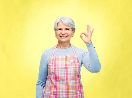 smiling senior woman in apron showing ok gesture Фото со стока