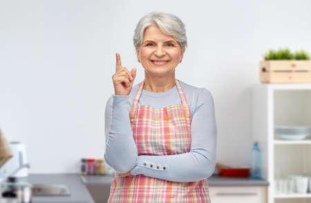 smiling senior woman pointing finger up at kitchen
