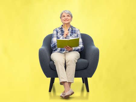 smiling senior woman in armchair writing to diary Фото со стока