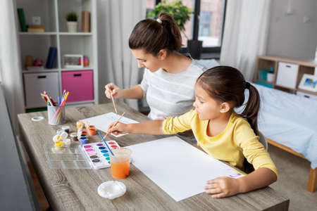 mother with little daughter drawing at home