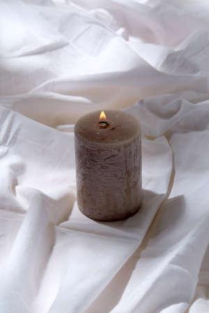 burning aroma candle on white sheet Фото со стока