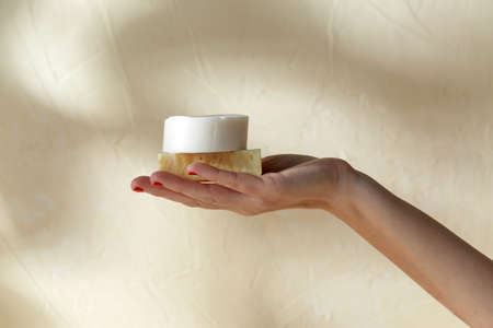 hand holding bar of craft soap on beige background