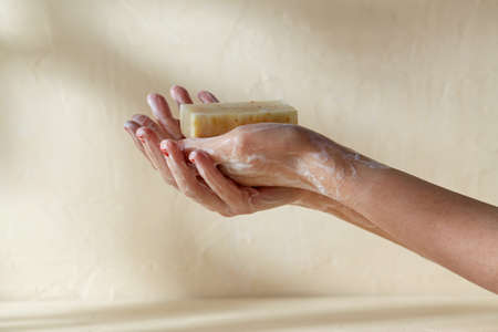 foamy hands holding bar of craft soap