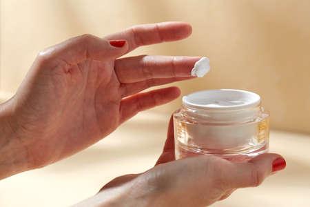 female hand holding jar of moisturizer