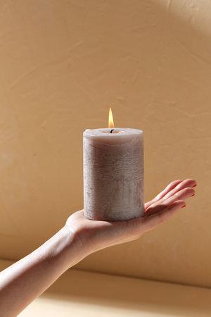 hand holding burning aroma candle on palm Фото со стока