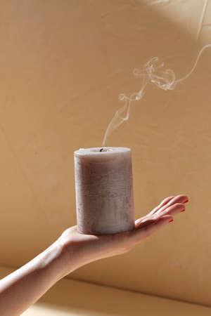 hand holding extinguished aroma candle on palm Фото со стока