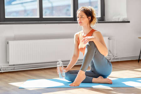 woman with water resting on yoga mat at home