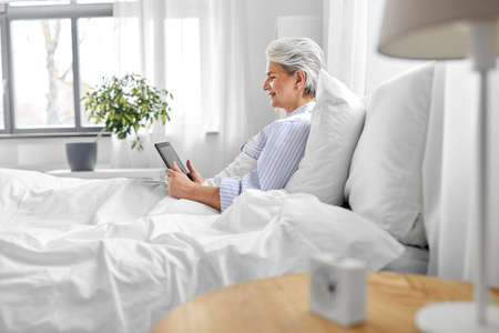 senior woman with tablet pc in bed at home bedroom Фото со стока