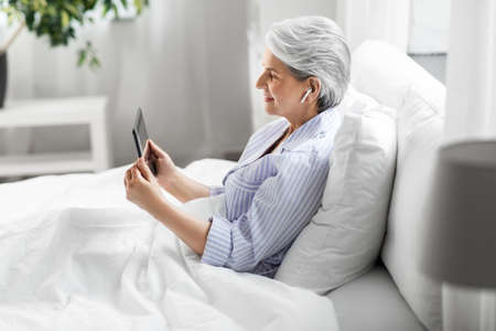 senior woman with tablet pc and earphones in bed