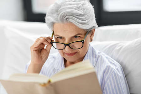 old woman in glasses reading book in bed at home