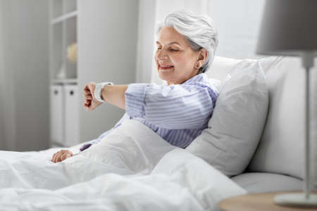 happy senior woman sitting in bed at home bedroom