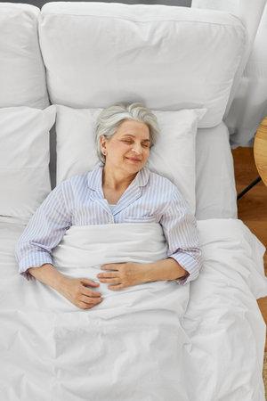 happy senior woman sleeping in bed at home bedroom